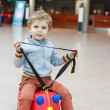 Funny toddler boy going on vacations trip with suitcase at airpo — Stock Photo