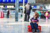 Little boy going on vacations trip with suitcase at airport — Stock Photo