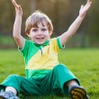 Blond boy of 4 playing soccer with football on football field — Stock Photo #44699435