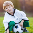 Blond boy of 4 playing soccer with football on football field — Stock Photo #44699631