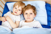 Little boys having fun in bed at home — Stock Photo