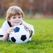 Blond boy of 4 playing soccer with football on football field — Stock Photo #44719113