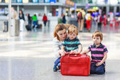 Mother and two little sibling boys at the airport — Стоковое фото