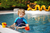 Schattig peuter spelen met water door het buitenzwembad — Stockfoto