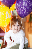 Happy little boy celebrating his 4 birthday with colorful balloo — Stock Photo