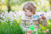 Happy little  boy in spring garden with blooming white flowers — Stock Photo