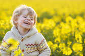 Happy little blond toddler boy lauging in yellow rape field on a — Stock Photo