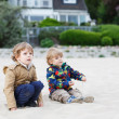 Two little children sitting on beach of river Elbe and playing t — Stock Photo #46979483