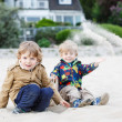 Two little children sitting on beach of river Elbe and playing t — Stock Photo #46979545