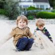 Two little sibling boys sitting on beach of river Elbe and playi — Stock Photo