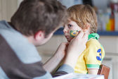 Father painting flag on face of little son — Stock Photo