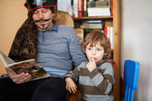 Father reading pirate book to his 4 years son, indoors — Stock Photo