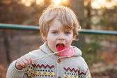 Portrait of beautiful little boy of 2 with big candy, outdoors — Stock Photo