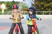 Two little siblings having fun on bikes in city on vacations — Stock Photo