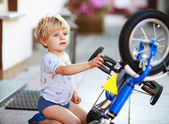 Happy funny toddler boy of two years repairing his first bike — Stock Photo