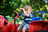 Funny little boy of three years playing on tractor — Stock Photo