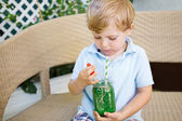 Little blond boy drinking healthy watermelon juice in summer. — Foto de Stock
