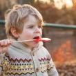 Portrait of beautiful little boy of 2 with big candy, outdoors — Stock Photo #47550225