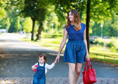 Happy young mother and adorable toddler girl walking through sum — Stock Photo