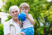 Happy grandfather playing with little grandchild ball — Stock Photo