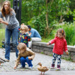 Mother and her children feeding ducks at summer — Stock Photo #48272069