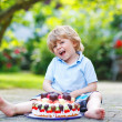Little boy celebrating his birthday in home's garden with big ca — Stock Photo
