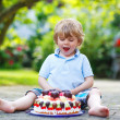 Little boy celebrating his birthday in home's garden with big ca — Stock Photo #48272829