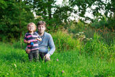 Little boy and his father sitting on grass in summer forest — Stock Photo