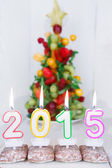 Burning candles with 2015 year and with fruit tree on background — Stock Photo