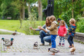 Mother and her children feeding ducks at summer — Stock Photo