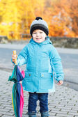 Portrait of adorable toddler boy with blue jacket and colorful u — Stock Photo