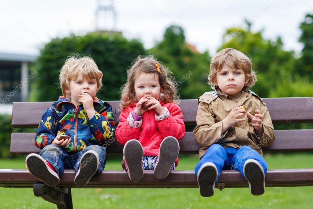 Twee kleine jongens en een meisje eten van chocolade stockfoto romrodinka 48272285 - Twee meisjes en een jongen ...