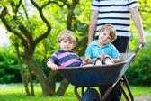 Two little boys having fun in wheelbarrow pushing by father — Stockfoto