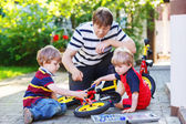 Father and two little sons reparing bikes together — Stockfoto