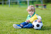 Blond boy of 3 playing soccer with football on football field — Stock Photo