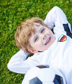 Blond boy of 4 resting with football on football field — Stock Photo
