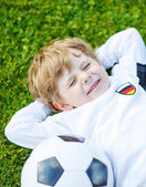 Blond boy of 4 resting with football on football field — Foto Stock