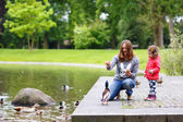 Mother and her daugther feeding ducks at summer — Stock Photo