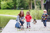 Mother and her children feeding ducks at summer — Stockfoto
