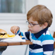 Little boy eating fast food: french fries and hamburger — Stock Photo #49048827