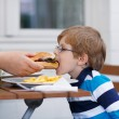 Little boy eating fast food: french fries and hamburger — Stock Photo #49048883