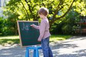 Маленький мальчик на доске практикующих математика — Стоковое фото