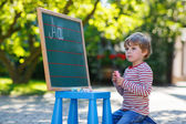 Little boy at blackboard practicing mathematics — Stock Photo