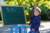 Little boy at blackboard practicing mathematics — Stock Photo