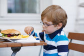 Little boy eating fast food: french fries and hamburger — Stockfoto