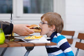 Little boy eating fast food: french fries and hamburger — Stock Photo