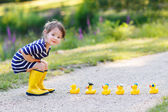 Adorable little girl with rubber ducks in summer park — Stock Photo
