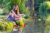 Adorable little girl and her mom playing with paper boats in a r — Stock Photo