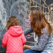 Happy mother and little daughter painting with chalk in park — Stock Photo #49050415