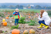 Young mother making picture of her son on pumpkin field. — Stockfoto